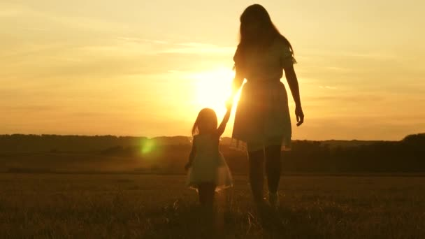 little daughter and mom walk around the field holding hands. baby holds moms hand. happy family walks in evening out of town. Mother and baby are resting in park. child plays with his mother in meadow