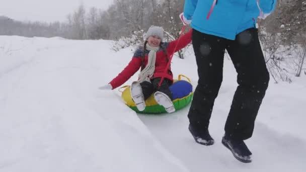Glückliche Kindheit. Winterurlaub für Familien. Kind und Mutter rodeln im Schnee. Tochter und Mutter spielen an den Weihnachtsfeiertagen im Winterpark.