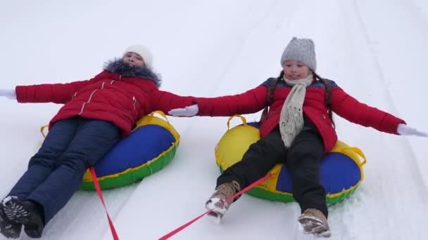 Kinderrodeln im Winter. Teenager spielen in den Weihnachtsferien im Winterpark. Konzept einer glücklichen Kindheit. Glückliches Familienkonzept.