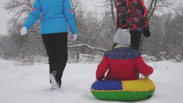 Anya és apa szánkóznak egy gyerekkel a téli erdőben. a szülők eljátsszák a kislányukat a karácsonyi parkban. A család egy téli parkban játszik karácsonykor. Lassú mozgás. boldog gyermekkori koncepció