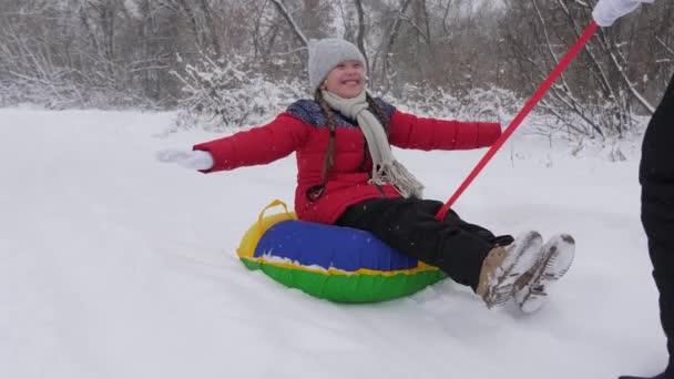 Kind und Mutter rodeln im Schnee. Tochter und Mutter spielen an den Weihnachtsfeiertagen im Winterpark. Winterurlaub für Familien. Konzept der glücklichen Kindheit
