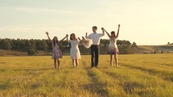 koncepce šťastné rodiny. matka, otec a malá dcera se sestrami procházející se na poli na slunci. Šťastná mladá rodina. Děti, táta a máma si hrají na louce na slunci.