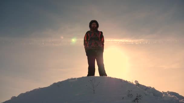 Az alaszkai utazó felmegy egy havas domb tetejére, és örül a téli naplemente elleni győzelemnek. Hegymászó Utazás a hegyekbe télen. Az alpinisták túráznak. Utazó megmászik egy hegycsúcsot.