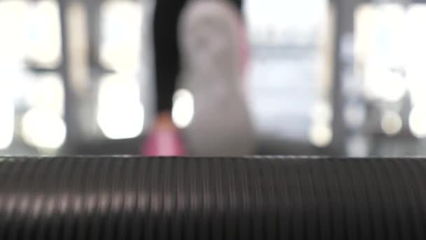 Laufband-Bewegung, Manntraining. Nahaufnahme. Die Beine des Mädchens in Turnschuhen gehen entlang des Laufbands. Stärkung der Beinmuskulatur beim Gehen. Cardio-Belastung. Sport Lifestylekonzept. Gewichtsverlust im Fitnessstudio.