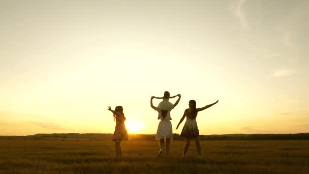 Šťastné dětství. Šťastná mladá rodina s dítětem běží přes pole za soumraku. Matka a dcery se procházejí v parku a hrají si na louce na slunci. koncepce života velké rodiny