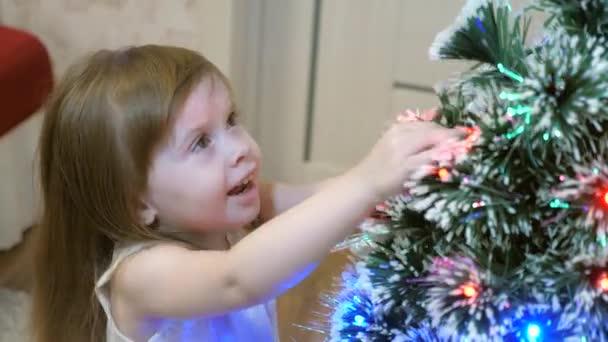 Holčička zkoumá věnce na vánočním stromečku. dítě hraje u vánočního stromku v dětském pokoji. krásný umělý vánoční stromek. Šťastné dětství. Rodinné hry na vánoční prázdniny