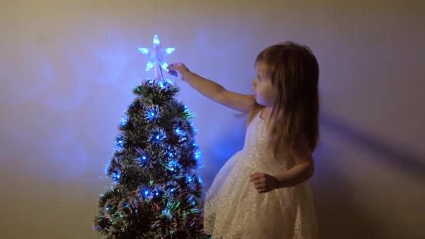 dítě zkoumá vánoční hvězdu na vánočním stromě. Holčička si hraje u vánočního stromečku v dětském pokoji. krásný umělý vánoční stromek. Koncept šťastného dětství.