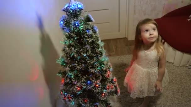 Šťastné dětství. malé dítě hraje u vánočního stromku v dětském pokoji. krásný umělý vánoční stromek. dcera zkoumá věnce na vánočním stromečku. Rodinné hry na vánoční prázdniny