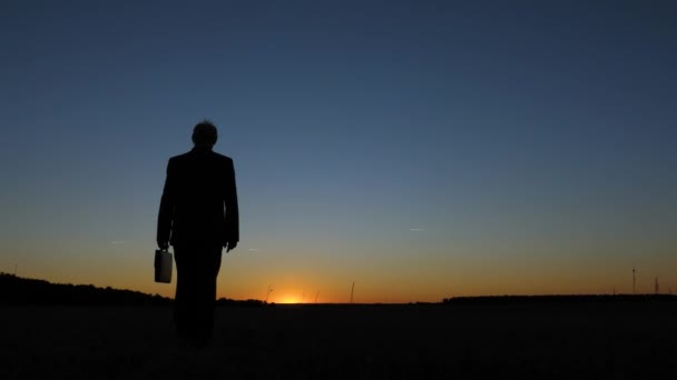 Silhouette man businessman in a business suit and with a briefcase in hand goes at sunset