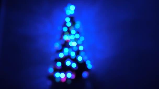 pestrobarevný bokeh novoroční stromeček v místnosti, zdobený zářivým věncem a hvězdou. dovolená pro děti i dospělé. Nový rok. Vánoční stromek, veselé svátky. Vánoční interiér.