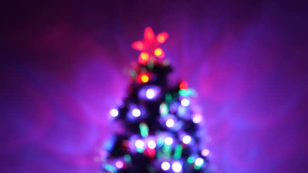 multi-colored bokeh of a New Year tree in the room, decorated with luminous garland and a star. holiday for children and adults. New Year. Christmas tree, happy holidays. Christmas interior.