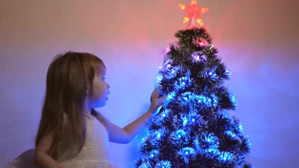 malé dítě hraje u vánočního stromku v dětském pokoji. dcera zkoumá věnce na vánočním stromečku. krásný umělý vánoční stromek. Šťastné dětství. Rodinné hry na vánoční prázdniny