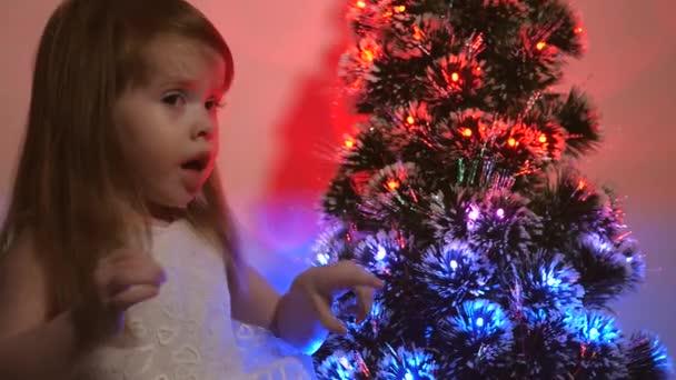 dcera zkoumá věnce na vánočním stromečku. malé dítě hraje u vánočního stromku v dětském pokoji. krásný umělý vánoční stromek. Šťastné dětství. Rodinné hry na vánoční prázdniny