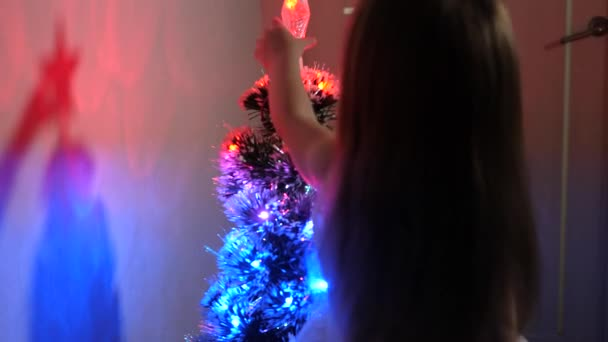kid plays for Christmas holidays. small child plays by Christmas tree in childrens room. daughter examines garland on Christmas tree. beautiful artificial christmas tree . happy childhood concept.