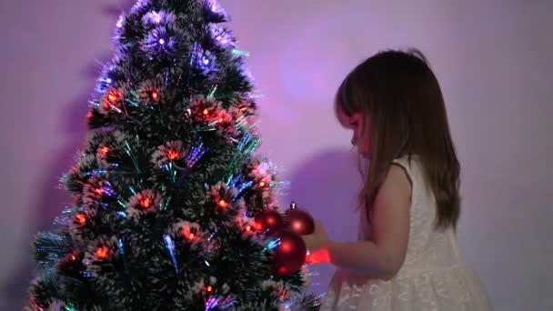 Kind schmückt den Weihnachtsbaum mit Weihnachtskugeln. Kleines Kind spielt am Weihnachtsbaum im Kinderzimmer. Tochter begutachtet Girlanden am Weihnachtsbaum Konzept der glücklichen Kindheit.
