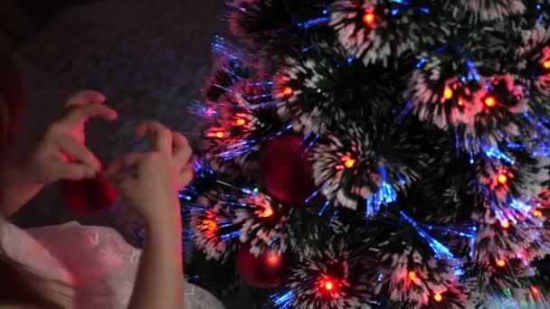 malé dítě hraje u vánočního stromku v dětském pokoji. dítě zdobí vánoční stromek s vánočními míčky. dcera zkoumá věnce na vánočním stromečku. koncept šťastného dětství.