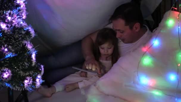 Tochter und Papa spielen an Heiligabend auf dem Tablet, im Kinderzimmer Girlanden. Konzept einer Familienweihnacht. Kind und Vater spielen im Zimmer. Konzept einer glücklichen Kindheit und Familie.