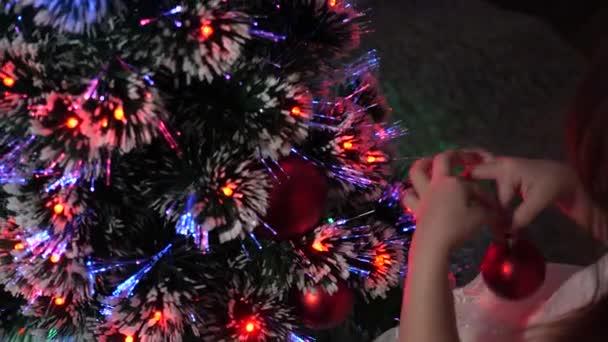 dítě zdobí vánoční stromek s vánočními míčky. malé dítě hraje u vánočního stromku v dětském pokoji. dcera zkoumá věnce na vánočním stromečku. koncept šťastného dětství.