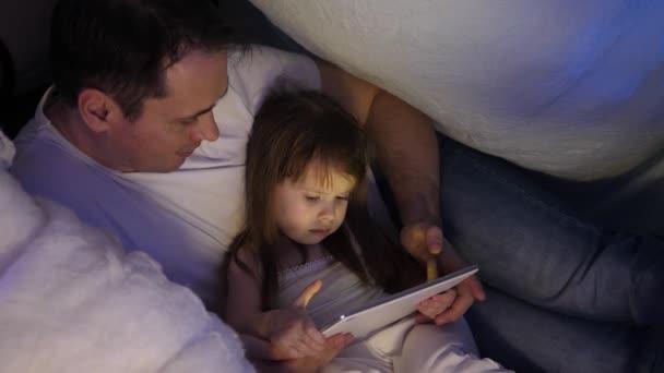 Konzept einer Familienweihnacht. Kind und Papa spielen an Heiligabend auf dem Tablet, im Kinderzimmer, im Zelt mit Girlanden. Baby und Vater spielen im Zimmer. Konzept einer glücklichen Kindheit und Familie.