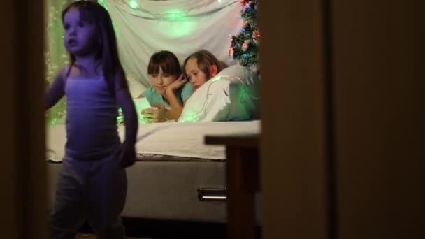 Děti si hrají v místnosti zdobené pestrobarevným novoročním stromem. sestry na Štědrý večer hrát na tabletu, v dětském pokoji na gauči, ve stanu s věnci. koncepce rodinných Vánoc.