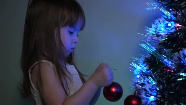 dítě zdobí vánoční stromek s vánočními míčky. detailní záběr. malé dítě hraje u vánočního stromku v dětském pokoji. dcera zkoumá věnce na vánočním stromečku. koncept šťastného dětství.