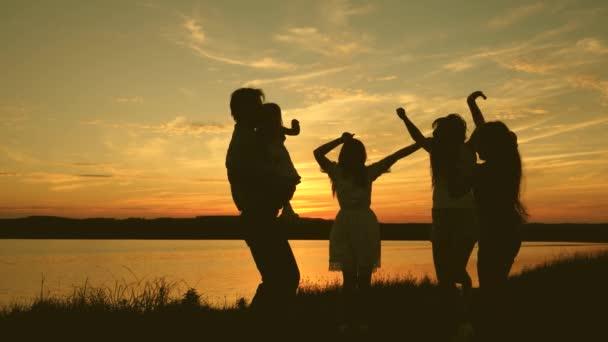 felice balli di famiglia sulla spiaggia. festa in riva al lago, bambini che ballano. ragazze felici che ballano sulla spiaggia. Rallentatore. belle ragazze divertirsi ascoltando musica. adolescenti fidanzate vacanza discoteca.