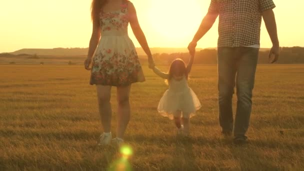 little daughter jumping holding hands of dad and mom in park on background of sun. Family concept. child plays with dad and mom on field in sunset light. Walking with a small kid in nature.