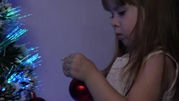Šťastné dětství. dítě zdobí vánoční stromek s vánočními míčky. detailní záběr. malé dítě hraje u vánočního stromku v dětském pokoji. dcera zkoumá věnce na vánočním stromě.