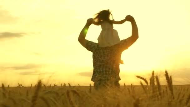 dítě a otec si hrají na poli zrající pšenice. Dcera na ramenou otce. Malý chlapec a táta cestují po poli. děti a rodiče si hrají v přírodě. šťastný rodinný a dětský koncept