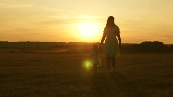 happy childhood concept. Happy mom and baby are walking on field at sunset holding hands. little girl and mother walk together on a in park in sunshine and smile. Family life concept. Slow motion