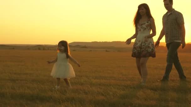 Buon bambino e genitori giocano al tramonto. Papà e madre si ritrovano con la figlia e il bambino ride e fugge. Silhouette di una famiglia che cammina al sole. Mamma papà e bambino. concetto di famiglia felice.