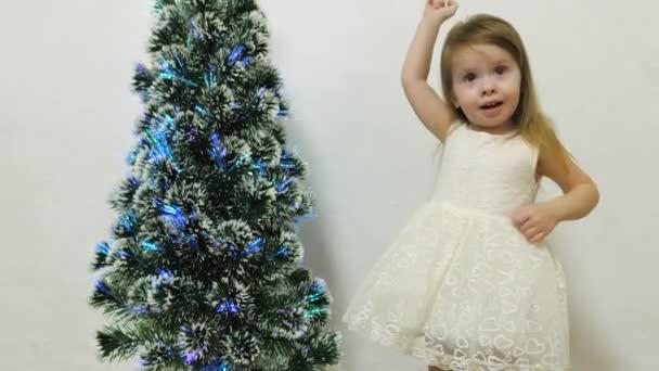 holčička si hraje poblíž vánočního stromečku v dětském pokoji s kočkou. Dětský a vánoční stromek. Vánoční prázdniny