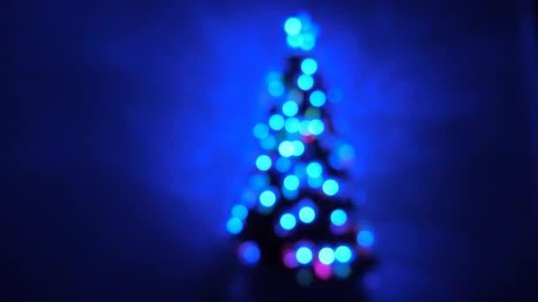 Karácsonyi belső. sokszínű bokeh egy újévi fa a szobában, díszített fényes koszorú és egy csillag. nyaralás gyermekek és felnőttek számára. Újév. Karácsonyfa, boldog ünnepeket.