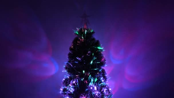 multi-colored Christmas tree, happy holidays. New Year 2020 mood. Christmas interior. beautiful Christmas tree in room, decorated with a luminous garland and star. holiday for children and adults.