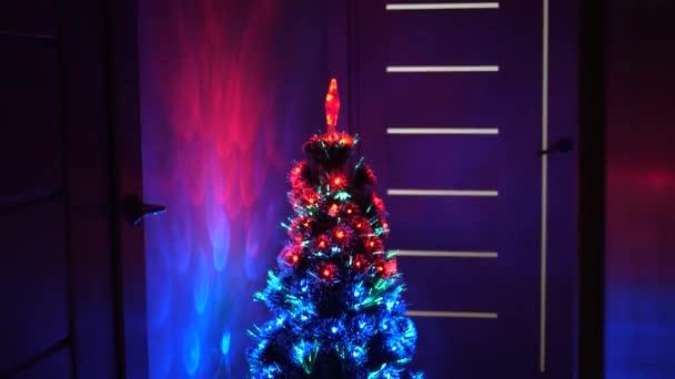 pestrobarevný vánoční stromek, veselé svátky. Nový rok 2020 nálada. Vánoční interiér. krásný vánoční stromek v pokoji, zdobený zářivým věncem a hvězdou. dovolená pro děti a dospělé.