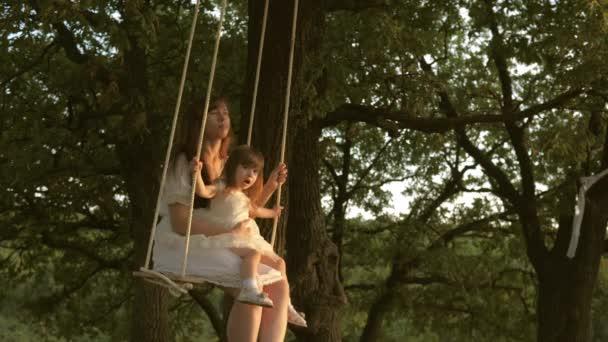 Máma otřásá dcerou pod stromem na slunci. Close-up. matka a dítě jedou po laně na dubové větvi v lese. Dívka se směje, radní. Rodinná zábava v parku, v přírodě. teplý letní den.