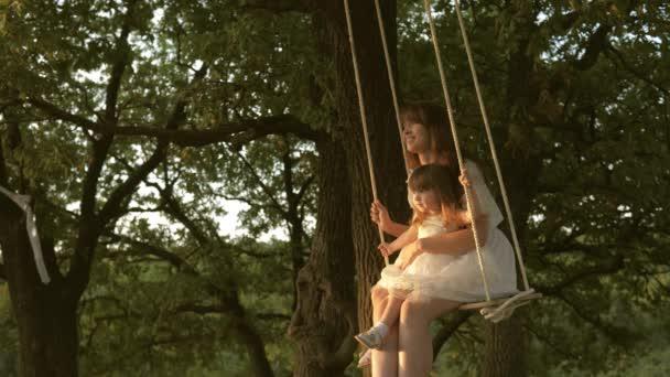 matka a dítě jezdit na laně houpačka na dubové větvi v lese. Děvče se směje, raduje. Rodinná zábava v parku, v přírodě. Máma třese dcerou na houpačce pod stromem na slunci. close-up.