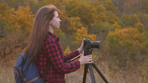 A fényképezőgéppel utazó lány gyönyörű képeket készít a természetről. Fiatal független női turisztikai fotós, fényképek egy gyönyörű őszi táj egy professzionális digitális fényképezőgép. utazási koncepció