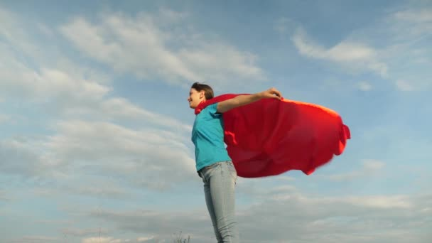 A gyerek piros kabátban játszik, arról álmodik, hogy hős szupernő lesz. Gyönyörű lány szuperhős áll a pályán egy piros köpenyben, köpeny repked a szélben. Lassú mozgás. A lány arról álmodik, hogy szuperhős lesz..