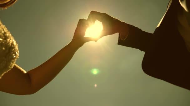 nap a kezében. Sziluettje egy szerető pár hogy a szív szimbólum a kezüket szemben a nap a horizonton. szerető párok csapatmunkában. Esküvő ünnepe