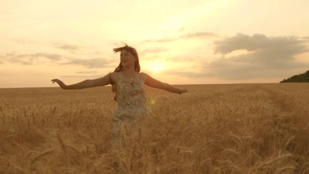 Šťastná mladá dívka běží zpomaleně přes pole a rukou se dotýká uší pšenice. Krásná volná žena těší přírodu v teplém slunci v pšeničném poli na pozadí západu slunce. dívka cestuje.