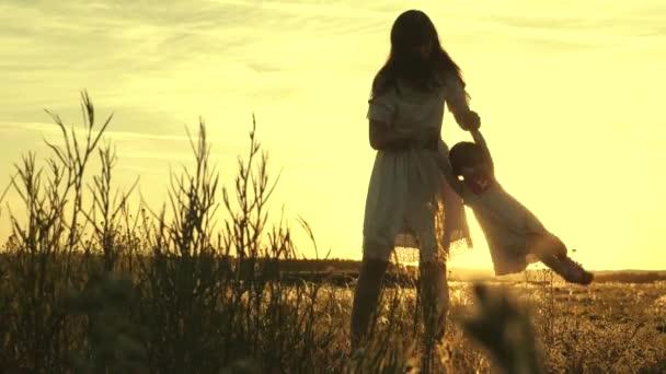 Máma houpe svým oblíbeným dítětem, drží se za ruce a dítě se za letu směje. Šťastné dítě si hraje na létání s matkou při západu slunce. Silueta ženy a dítěte. Pojem rodina a dětství