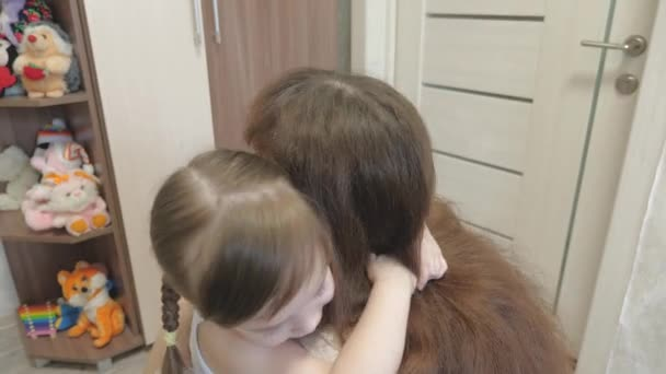 Happy loving daughter hugs a cute mom. little baby hugs mother. happy family is playing. the baby clings tightly to the mother and kisses her. maternity and laugh day concept