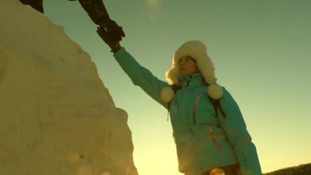 Zdarma žena cestovatel vylézt na horu držet za ruce. horolezci lezou na horu. pracovat v týmu turistů. výlet do hor při západu slunce. obchodníci se pojistí navzájem.