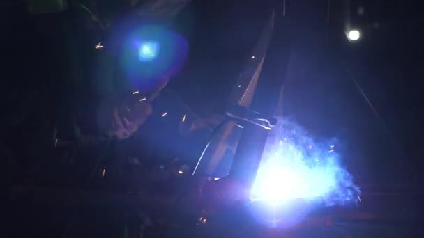 Industriearbeiter in Schutzmaske mit einem modernen Schweißgerät zum Schweißen von Metallkonstruktionen in der industriellen Produktion in einem metallverarbeitenden Betrieb. helles Licht und Funken beim Schweißen.