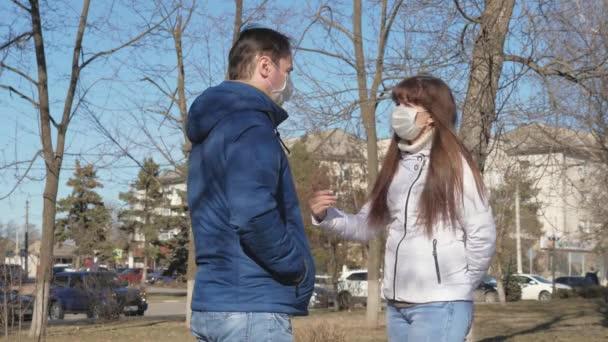 muž a žena v ochranné masce proti virům a bakteriím mluví na ulici. Pandemický koronavirus. turisté na ulici nosí ochrannou masku před viry. koncepce zdraví a bezpečnosti, N1H1