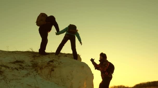 hegymászók csapata felmászik egy hegyre, segítő kezet nyújtva egymásnak. Szabad nő utazó mászni hegyet. Turisták csapatmunkája. Utazás és kaland a hegyekben naplementekor.