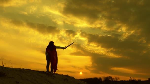 szuper nő egy karddal a kezében, és egy piros köpenyben áll egy hegyen a naplemente fényénél. Szabad nő, aki szuperhőst játszik. lány játszik római lenin fényes sugarak a nap ellen az ég