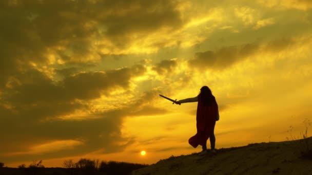 Egy szabad nő karddal a kezében, vörös köpenyben áll a hegyen, és a naplementét nézi. A szabad lány szuperhőst játszik. lány játszik romlenina a vörös sugarak a nap ellen ég