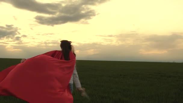 Szabad lány piros köpenyben, karddal a kezében fut át a mezőn, középkori lovagot játszva. fiatal lány szuperhősöket játszik. Gyerek lovagosat játszik. A gyerekek játékkarddal harcolnak. boldog gyermekkort